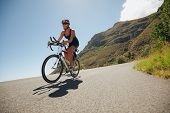 picture of triathlon  - Woman competing in the cycling leg of a triathlon with competitor - JPG