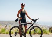 stock photo of triathlon  - Portrait of confident young female cyclist standing with her bicycle on country road - JPG