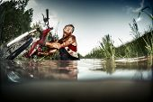 stock photo of swamps  - Young man athlete with dirty stained clothes pulling his bicycle from the swamp - JPG