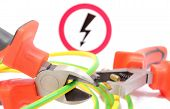 stock photo of pliers  - Metal pliers with green yellow electric cable and high voltage danger sign in background pliers cut the cable - JPG
