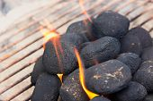 image of briquette  - Charcoal briquettes on fire in a BBQ - JPG