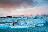 stock photo of iceberg  - Icebergs drifting to sea in Jokulsarlon during winter Iceland - JPG