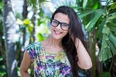 image of palm-reading  - Smiling beautiful brunette looking at camera with palm tree behind her - JPG