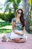 stock photo of palm-reading  - Smiling beautiful brunette sitting and reading a book with palm tree behind her - JPG