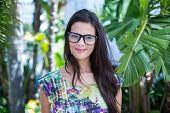 pic of palm-reading  - Smiling beautiful brunette looking at camera with palm tree behind her - JPG