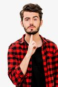stock photo of handgun  - Handsome young man looking at cameraand gesturing handgun while standing against white background - JPG