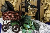 image of wood craft  - antique craft baby carriage on ivy and lace with wicker chair and wood background - JPG