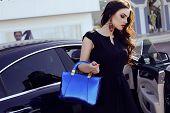 foto of wearing dress  - fashion outdoor photo of beautiful sensual woman with long dark hair wearing elegant black dress with bag posing beside a luxurious auto - JPG