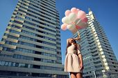 stock photo of high-rise  - Beautiful young girl holding colored balloons over high - JPG