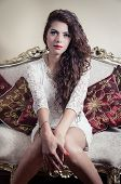 stock photo of bolivar  - Pretty model girl wearing white dress sitting on victorian sofa looking into camera - JPG