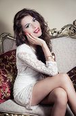 stock photo of mystique  - Pretty model girl wearing white dress sitting on victorian sofa posing for camera with smile and legs crossed - JPG