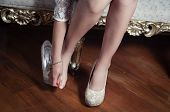 picture of bolivar  - closeup leg caption of model girl wearing white dress sitting on victorian sofa using left shoe holding  hand over right toes - JPG