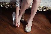 foto of bolivar  - closeup leg caption of model girl wearing white dress sitting on victorian sofa using left shoe holding  hand over right toes - JPG