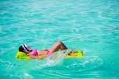 picture of legs air  - Happy Woman relaxing on inflatable air mattress at turquoise water - JPG