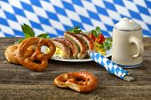 picture of pretzels  - Fried Bavarian sausages on potato salad served with pretzels and half a liter of Bavarian beer in a tankard - JPG