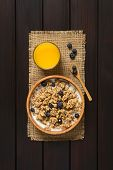 picture of cereal bowl  - Dried berry and oatmeal breakfast cereal with fresh blueberries and milk in wooden bowl with a glass of juice photographed overhead on dark wood with natural light - JPG
