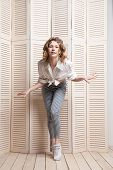 foto of jalousie  - Beautiful woman wearing pants and shirt dancing in front of a jalousie - JPG