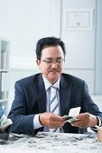 picture of financial management  - Vietnamese financial manager counting money at office - JPG