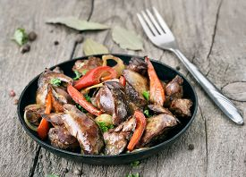 foto of liver fry  - Fried chicken liver with vegetables in frying pan and fork on wooden table - JPG