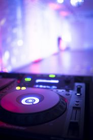 stock photo of social housing  - DJ console cd mp4 deejay mixing desk Ibiza house music party in nightclub with colored disco lights.