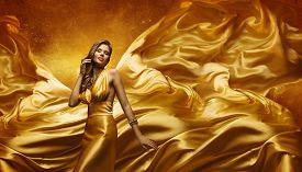 image of flutter  - Fashion Model in Gold Dress Beauty Woman Posing over Flying Waving Cloth Girl with Yellow Dynamic Silk Fabric - JPG