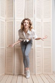 picture of jalousie  - Beautiful woman wearing pants and shirt dancing in front of a jalousie - JPG