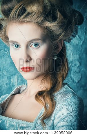 Fashion portrait of a beautiful woman in a luxurious medieval dress and high hairdo in vintage style