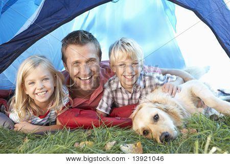 Постер, плакат: Молодой отец позы с детьми в палатке