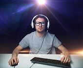 technology, gaming, entertainment, lets play and people concept - young man in headset and eyeglass poster