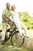 stock photo of middle-age  - Mature couple riding bike in countryside - JPG