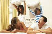 Young Family Having Pillow Fight In Bedroom