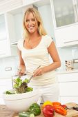 stock photo of blonde woman  - Woman Preparing Salad In Modern Kitchen - JPG