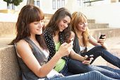 stock photo of mobile-phone  - Group Of Teenage Students Sitting Outside On College Steps Using Mobile Phone - JPG