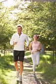 stock photo of middle-age  - Middle Aged Couple Jogging In Park - JPG