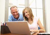 Vater und Tochter im Teenageralter mit Laptop zu Hause