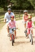 stock photo of family fun  - Family Cycling In Countryside Wearing Safety Helmets - JPG