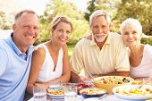 Adult Son And Daughter Enjoying Meal In Garden With Senior Parents