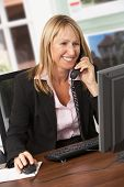 stock photo of real-estate agent  - Female Estate Agent Talking On Phone At Desk - JPG