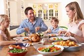 picture of roast chicken  - Happy family having roast chicken dinner at table - JPG