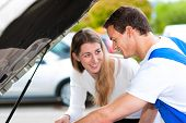 Woman talking to a car mechanic in a parking area, both are standing next to the car