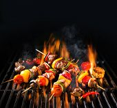 Barbecue skewers meat kebabs with vegetables on flaming grill poster