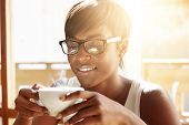 People, Drinks And Leisure Concept: Happy Dark-skinned Woman Wearing Glasses, Drinking Tea From Cup poster