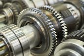 close-up metal cog wheels in gearing at gear box poster