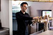 Handsome barkeeper pouring beer in glass from faucet at bar counter poster