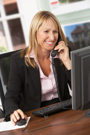 stock photo of real-estate agent  - Female Estate Agent Talking On Phone At Desk - JPG