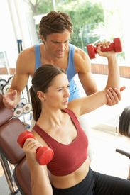 stock photo of weight-lifting  - Young Woman Working With Weights In Gym With Personal Trainer - JPG