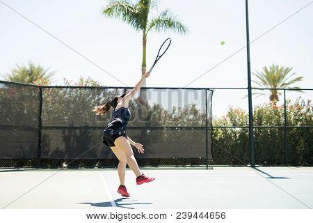 Female Tennis Player Hitting The