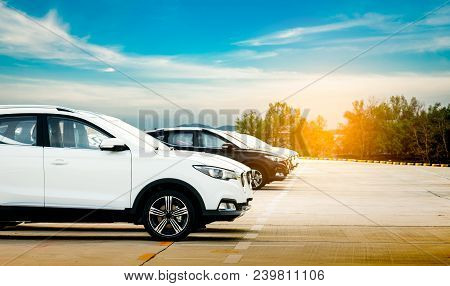 poster of Luxury White And Black New Suv Car Parked On Concrete Parking Area At Factory With Blue Sky And Clou