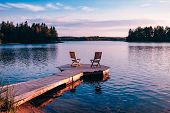 Two Wooden Chairs On A Wood Pier Overlooking A Lake At Sunset poster