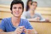 Student listening to a lecturer while looking at the camera